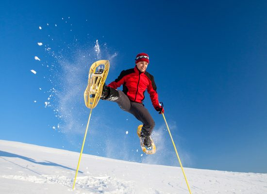 Young man having fun while snowshoeing outdoors on a lovely snowy winter day